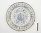 Plat en faïence de Delft au décor de tiges fleuries dans un médaillon